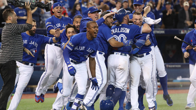 TORONTO, ON - OCTOBER 09: Josh Donaldson #20 of the Toronto Blue Jays is congratulated by teammates after scoring the game-winning run in the tenth inning during MLB game action against the Texas Rangers in game three of the American League Divison Series at Rogers Centre on October 9, 2016 in Toronto, Canada. (Photo by Tom Szczerbowski/Getty Images)